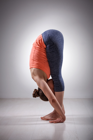 bending forward: Sporty fit woman practices bending yoga asana Uttanasana - standing forward bend pose Stock Photo