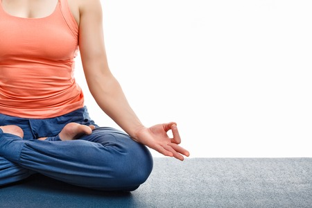 copyspace: Close up of woman doing yoga asana Padmasana (Lotus pose) cross legged position for meditation with Chin Mudra - psychic gesture of consciousness. Isolated on white background with copyspace Stock Photo