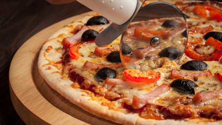 pizza cutter: Letterbox panorama of pizza cutter (wheel) slicing ham pizza with capsicum and olives on wooden board on table