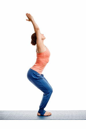 ashtanga: Sporty fit woman doing Surya Namaskar ashtanga vinyasa yoga asana Utkatasana - chair pose isolated on white