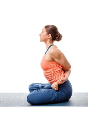 baddha: Sporty fit woman doing  Ashtanga Vinyasa yoga asana Baddha Padmasana - bound restrained lotus pose isolated on white