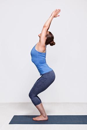 namaskar: Sporty fit woman doing Surya Namaskar ashtanga vinyasa yoga asana Utkatasana - chair pose Stock Photo