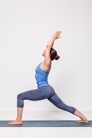 yogini: Beautiful sporty fit yogini woman practices yoga asana Virabhadrasana 1 - warrior pose 1 Stock Photo