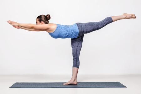 Beautiful sporty fit woman practices yoga asana Virabhadrasana 3 - warrior 3 pose