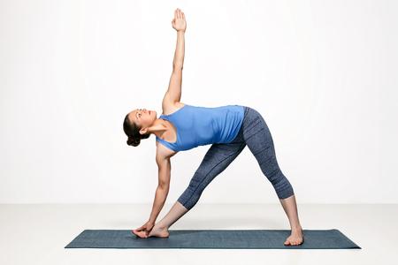 Beautiful sporty fit woman practices Ashtanga Vinyasa yoga asana utthita trikonasana - extended triangle pose