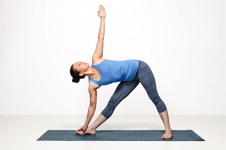 Beautiful sporty fit woman practices Ashtanga Vinyasa yoga asana utthita trikonasana - extended triangle pose
