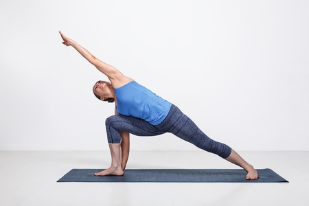 parsvakonasana: Young fit woman doing Ashtanga Vinyasa Yoga asana Utthita parsvakonasana - extended side angle pose advanced variation
