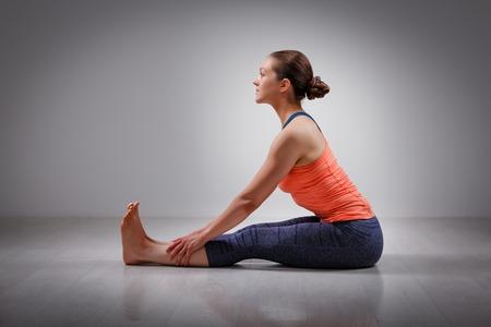 beginner: Sporty fit woman practices Ashtanga Vinyasa yoga back bending asana Paschimottanasana - seated forward bend beginner variation