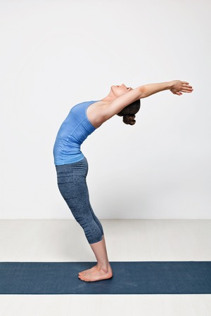 bends: Beautiful sporty fit woman practices Sivananmda yoga asana Anuvittasana  - standing back bend pose
