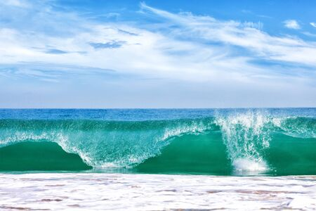 Big wave in ocean with blue sky