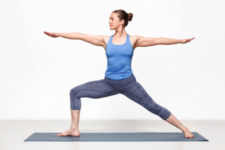 positions: Beautiful sporty fit yogini woman practices yoga asana Virabhadrasana 2 - warrior pose 2