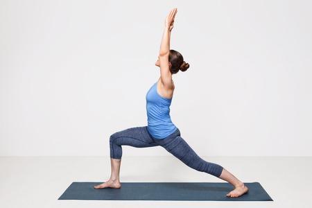 Beautiful sporty fit yogini woman practices yoga asana Virabhadrasana 1 - warrior pose 1 스톡 콘텐츠