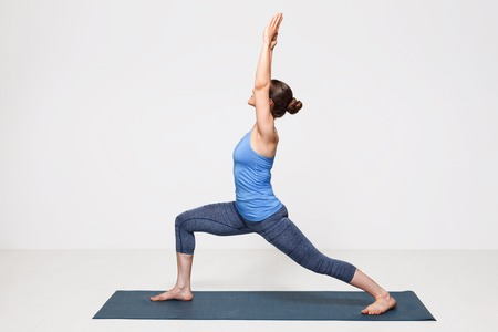 Beautiful sporty fit yogini woman practices yoga asana Virabhadrasana 1 - warrior pose 1 Stockfoto