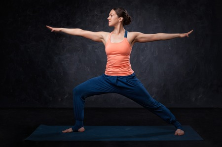 asana: Beautiful sporty fit yogini woman practices yoga asana Virabhadrasana 2 - warrior pose 2 on dark background
