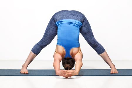 ashtanga: Beautiful sporty fit woman practices Ashtanga Vinyasa yoga asana Prasarita padottanasana C - wide legged forward bend C