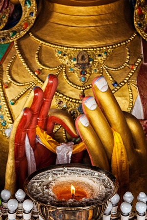 maitreya: Maitreya Buddha hands with burning lampion in Thiksey Gompa. Ladakh, India