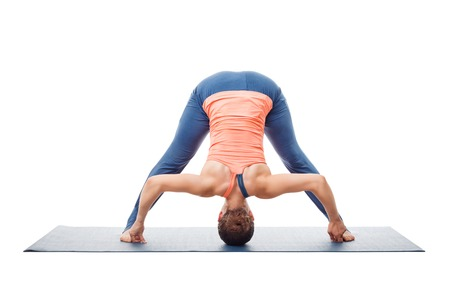 ashtanga: Beautiful sporty fit woman practices Ashtanga Vinyasa yoga asana Prasarita padottanasana D - wide legged forward bend D isolated on white background