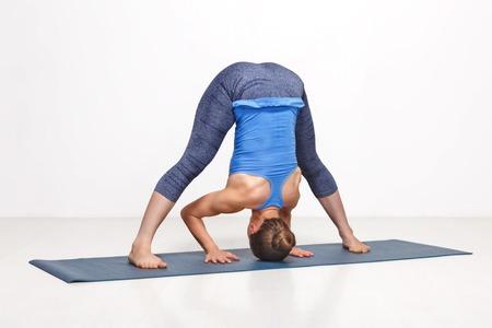 ashtanga: Beautiful sporty fit woman practices Ashtanga Vinyasa yoga asana Prasarita padottanasana B - wide legged forward bend B Stock Photo