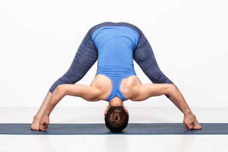 ashtanga: Beautiful sporty fit woman practices Ashtanga Vinyasa yoga asana Prasarita padottanasana D - wide legged forward bend D Stock Photo