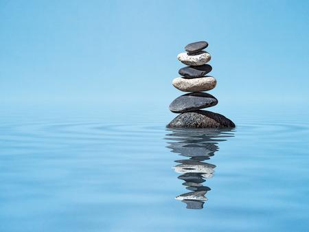 Zen harmonie méditation relaxation tranquillité tranquillité d'esprit concept background - pierres équilibrées empiler dans l'eau avec réflexion