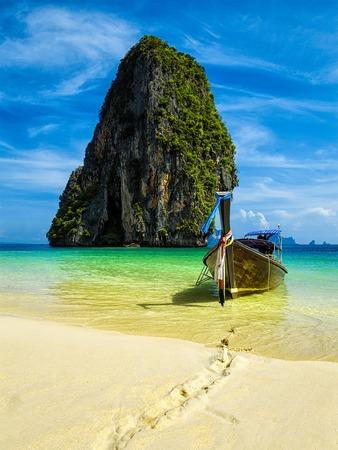 Bateau à longue queue sur la plage tropicale avec des roches calcaires, Krabi, Thaïlande