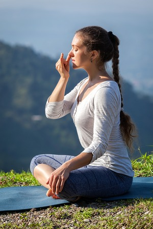 Woman practices pranayama yoga breath control in lotus pose padmasana outdoors in Himalayas in the morning on sunrise. Himachal Pradesh, India 스톡 콘텐츠