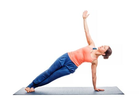 side pose: Beautiful sporty fit woman practices yoga asana Vasisthasana - side plank pose isolated on white