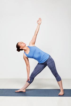trikonasana: Beautiful sporty fit woman practices yoga asana utthita trikonasana - extended triangle pose beginner variation Stock Photo
