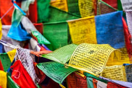 hum: Tibetan Buddhism prayer flags (lungta) with prayer mantra Om mani padme hum in tibetan language. Leh, Ladakh, Jammu and Kashmir, India