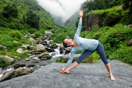 woman pose: Woman doing Ashtanga Vinyasa yoga asana Utthita trikonasana - extended triangle pose outdoors at waterfall in Himalayas