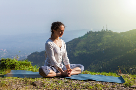 lass: Sporty fit woman practices yoga asana Baddha Konasana - bound angle pose outdoors in Himalayas mountains in the morning. Himachal Pradesh, India Stock Photo