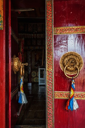 gompa: Open leaf of gate of Spituk Gompa (Tibetan Buddhist monastery) with ornamented decorated door handle. Ladakh, India