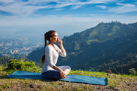 Woman practices pranayama yoga breath control in lotus pose padmasana outdoors in Himalayas in the morning on sunrise. Himachal Pradesh, India Standard-Bild
