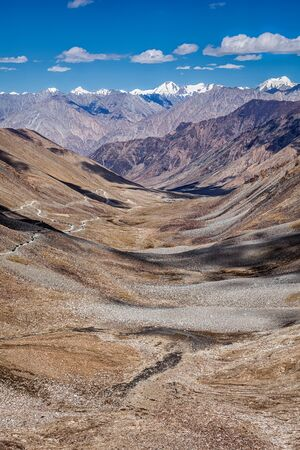 twisty: View of Karakorum range and road in valley  from Kardung La - the highest motorable pass in the world (5602 m). Ladakh, India
