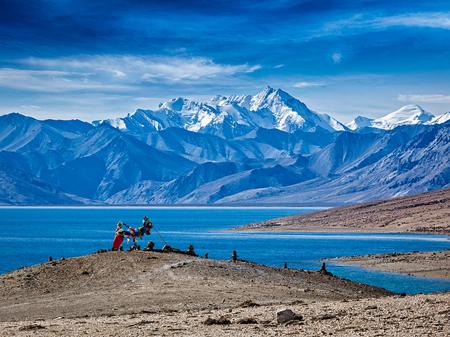 himalayas: Buddhist prayer flags lungta at Himalayan lake Tso Moriri in the morning. Korzok, Ladakh, Jammu and Kashmir, India Stock Photo