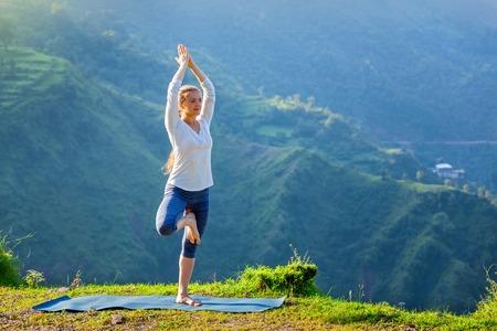 slim girl: Woman practices balance yoga asana Vrikshasana tree pose in Himalayas mountains outdoors in the morning. Himachal Pradesh, India
