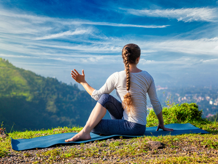 parivrtta: Sporty fit woman practices yoga asana Parivrtta Marichyasana -  seated spinal twist outdoors in mountains in the  morning