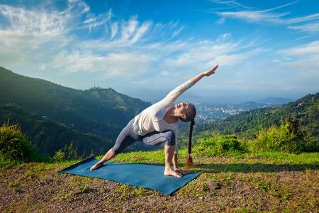 la mujer del ajuste deportivo practica yoga asana Utthita Parsvakonasana - pose de ángulo lateral extendida al aire libre en las montañas de la mañana