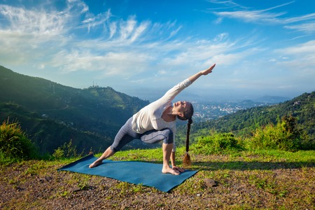side pose: Sporty fit woman practices yoga asana Utthita Parsvakonasana -  extended side angle pose outdoors in mountains in the  morning