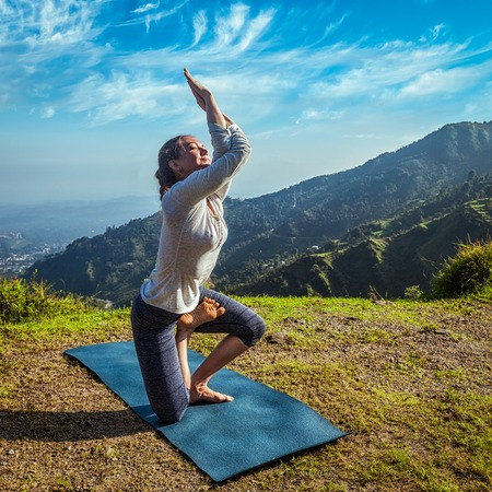 healthy girl: Young woman doing Ashtanga Vinyasa yoga advanced difficult asana Vatayanasana (Horse pose) outdoors in Himalayas mountains. Himachal Pradesh, India Stock Photo