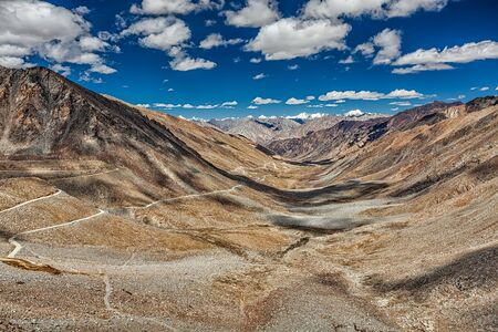 twisty: View of Karakoram range and road in valley  from Kardung La - the highest motorable pass in the world (5602 m). Ladakh, India