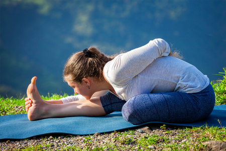 baddha: Woman doing Ashtanga Vinyasa yoga asana Ardha baddha padma paschimottanasana half bound lotus intense west stretch poser outdoors in mountains in the morning in Himalayas