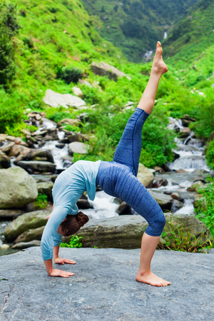 pada: Woman doing yoga asana eka pada urdva dhanurasana Upward Bow Pose outdoors at waterfall in Himalayas