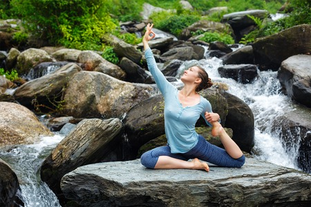 pada: Young sporty fit woman doing yoga asana Eka pada rajakapotasana - one-legged king pigeon pose at tropical waterfall. Himachal Pradesh, India Stock Photo