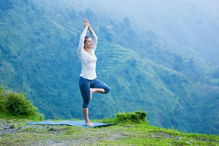 Woman practices balance yoga asana Vrikshasana tree pose in Himalayas mountains outdoors. Himachal Pradesh, India. Panorama Stock Photo