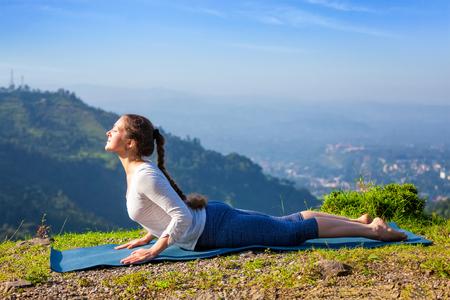 bhujangasana: Beautiful sporty fit woman practices yoga asana bhujangasana - cobra pose beginner variation outdoors in mountains in the morning