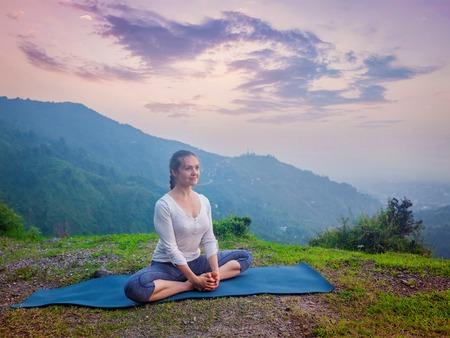 baddha: Sporty fit woman practices yoga asana Baddha Konasana - bound angle pose outdoors in HImalayas mountains on sunset. Himachal Pradesh, India Stock Photo