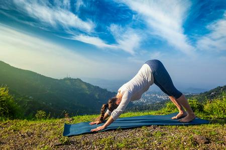 namaskar: Young sporty fit woman doing yoga asana Adho mukha svanasana - downward facing dog - in Surya Namaskar Sun Salutation outdoors in Himalayas in the morning