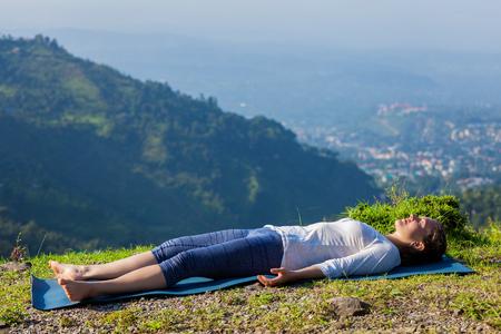 Woman relaxes in yoga asana Savasana - corpse pose outdoors in Himalayas. Himachal Pradesh, India Stockfoto