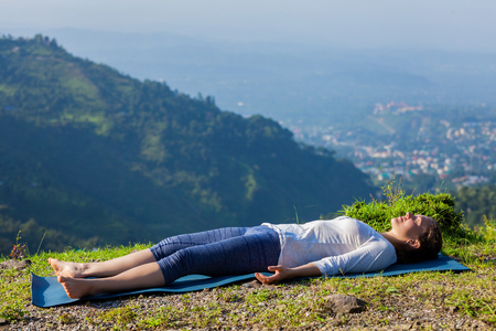 Woman relaxes in yoga asana Savasana - corpse pose outdoors in Himalayas. Himachal Pradesh, India Banco de Imagens